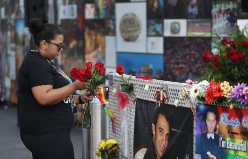 A woman places flowers on a fence at the memorial set up for the shooting victims at Pulse in 2018