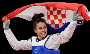 Matea Jelic smiles and raises the flag of Croatia behind her in celebration