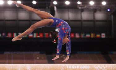 Simone Biles performs a back-handspring on balance beam during the qualification round of the women's artistic gymnastics competition in Tokyo.