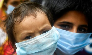 Children wear facemasks and wait in a queue with others to take swab samples to test for the Covid-19 coronavirus