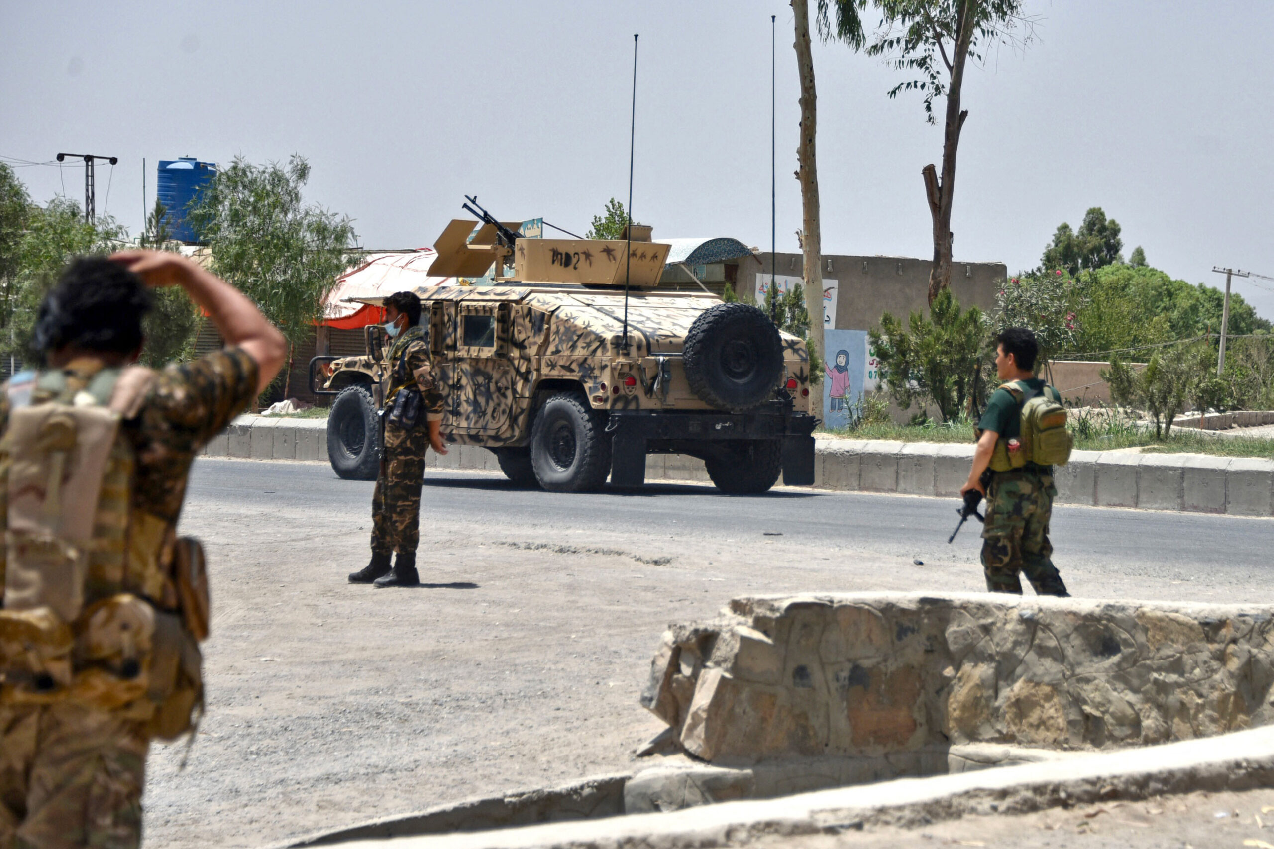 <i>Javed Tanveer/AFP/Getty Images</i><br/>Afghan security personnel stand guard along a road during an ongoing fight between Afghan forces and Taliban fighters in Kandahar on July 9.