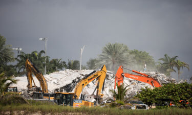 Rescue workers use excavators to dig through the rubble of the collapsed 12-story Champlain Towers South condo building on July 9 in Surfside
