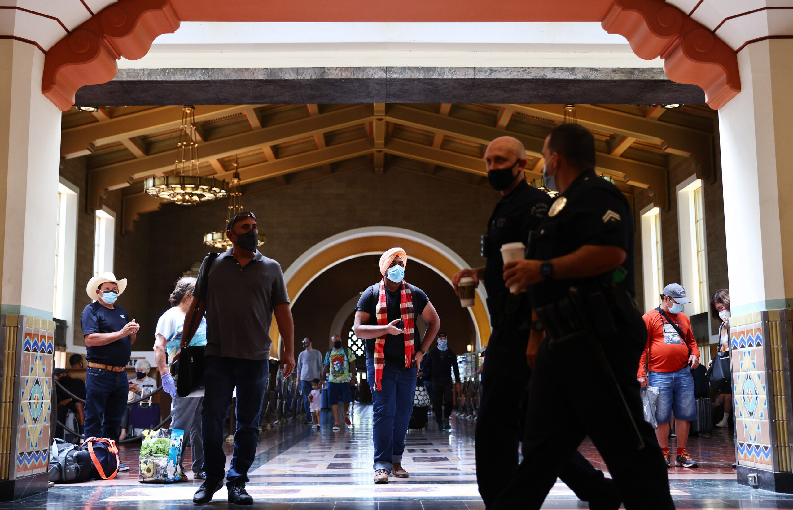 <i>Mario Tama/Getty Images</i><br/>People wear face coverings at Union Station in Los Angeles on July 19. Despite now having a powerful tool to help suppress the spread of coronavirus -- three very effective vaccines -- the nation is once again seeing rising cases