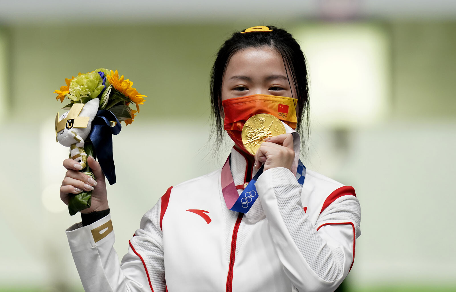 <i>Danny Lawson/PA Images/Getty Images</i><br/>China's Yang Qian celebrates with her gold medal after winning the 10m Air Rifle Women's Final on the first day of the Tokyo 2020 Olympic Games.