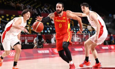 A Spanish basketball player dribbles the ball as two Japanese players chase after him on either side