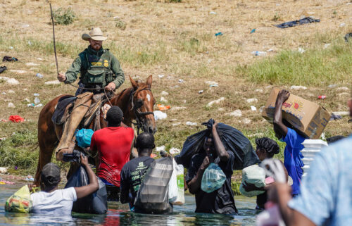 A United States Border Patrol agent on horseback uses the reins as he tries to stop Haitian migrants from entering an encampment. The DHS has since temporarily suspended the use of horse patrol.