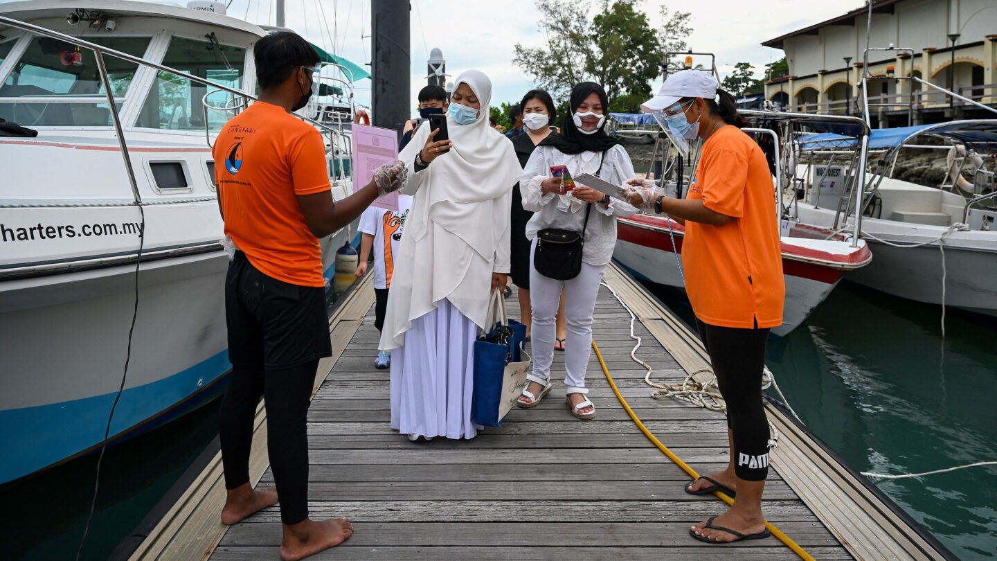 <i>MOHD RASFAN/AFP via Getty Images</i><br/>Passengers scan an app to monitor their health status before boarding a yacht in Langkawi