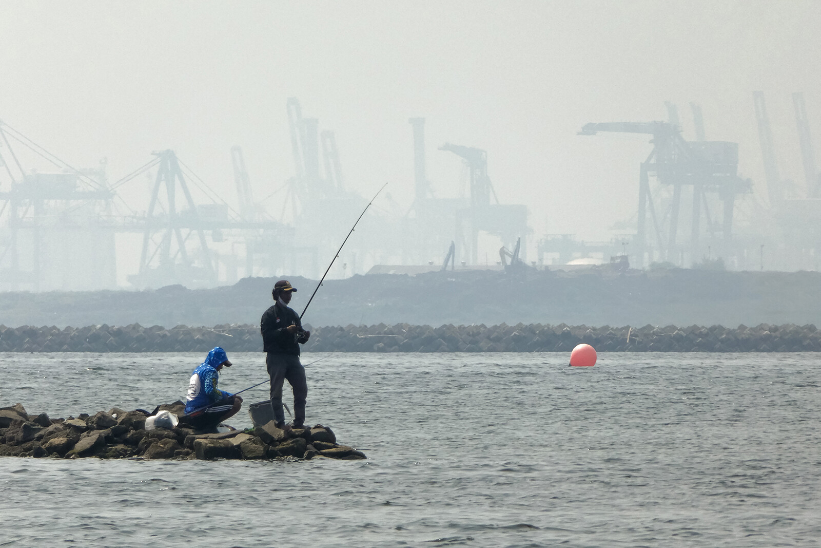 <i>Bay Ismoyo/AFP/Getty Images</i><br/>Anglers fish amid thick haze at a coastal area in Jakarta on June 20