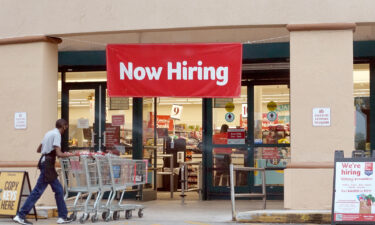 A Now Hiring sign hangs near the entrance to a Winn-Dixie Supermarket on September 21 in Hallandale