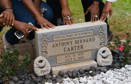 Family members touch the headstone for Anthony Bernard Carter following its unveiling in Hogansville