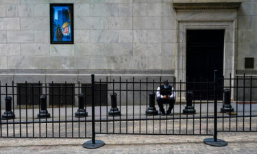 A stock broker takes a break outside the New York Stock Exchange